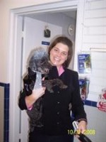 -Courtney dressed as Sarah Palin is holding her dog, Cosmo dressed as Don King, on Halloween Day.